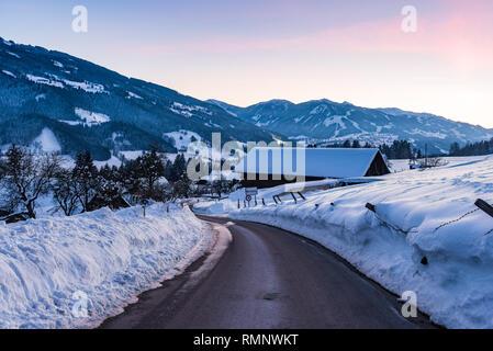 Empty asphalt road in winter Birnberg, Schladming, Schladming-Dachstein, Dachstein massif, Liezen District, Styria, Austria, Europe - Stock Photo