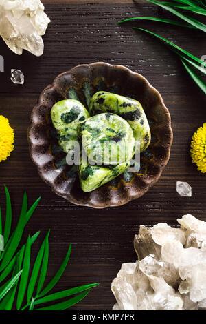 Nephrite Jade with Smoky Quartz and Mums on Dark Wood - Stock Photo