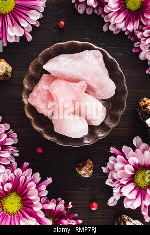 Rough Rose Quartz Crystals with Garnet and Pink Mums on Dark Table - Stock Photo