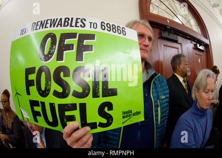 Mineola, New York, USA. 15th Feb, 2019. PHILIP MARINELLI, Huntington, is holding a green sign with Text Renewable to 69866 OFF FOSSIL FUELS on it, by food and water action, during NYS Senate Public Hearing on Climate, Community & Protection Act Bill S7253, sponsored by Sen. Kaminsky, Chair of Senate Standing Committee on Environmental Conservation. This 3rd public hearing on bill to fight climate change was on Long Island. Credit: Ann Parry/ZUMA Wire/Alamy Live News - Stock Photo