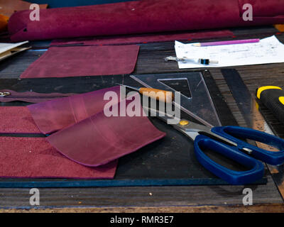Tools for leather crafting and pieces of Marsala leather Manufacture of leather - Stock Photo