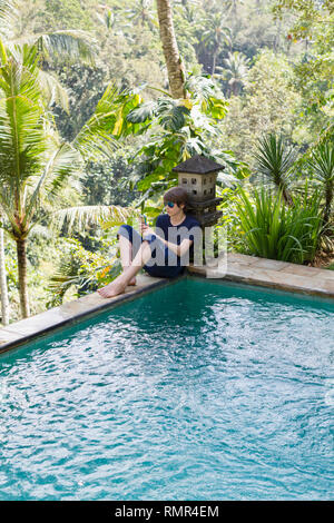 Teenage boy at swimming pool using cell phone - Stock Photo