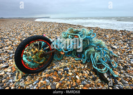 Old bike tangled in a plastic fishing net, discarded on a beach, East Sussex, UK - Stock Photo