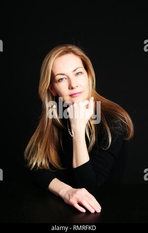 Close up studio portrait of a beautiful woman in the black dress against black background - Stock Photo