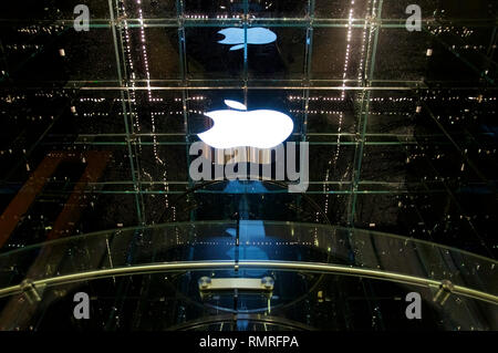 The lighted white logo of Apple at a flagship store in New York City's 5th Avenue at night. - Stock Photo