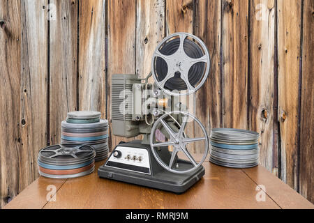 Vintage 8mm home movie projector and film cans with old wood wall. - Stock Photo