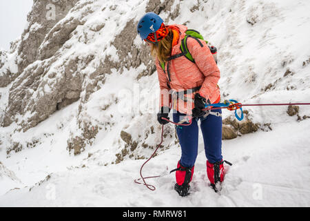 Young girl abseiling a steep rock into a narrow couloir covered in fresh snow, using a tube belay plate, backed up with a prusik friction knot on a 7.