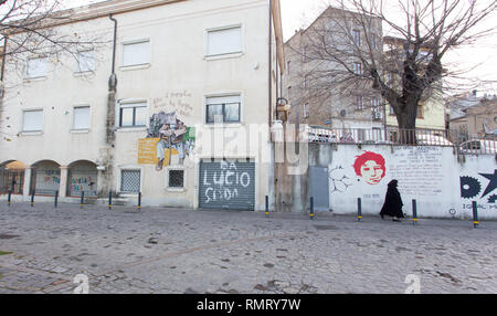 Orgosolo, Italy - December 29, 2018: a black dressed woman walking in front of famous murales in Orgosolo, Sardinia. - Stock Photo