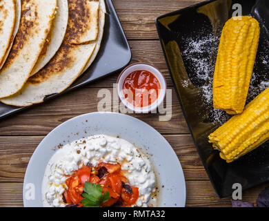 Quesadilla, salad with cottage cheese and tomatoes, two corn on wood table. - Stock Photo