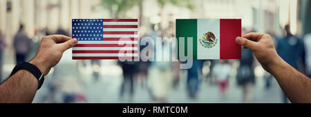 Two hands holding different flags, Mexico vs United States on politics arena over crowded street background. Future strategy, relations between countr - Stock Photo
