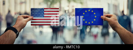 Two hands holding different flags, EU vs USA on politics arena over crowded street background. Future strategy, relations between countries. Cooperati - Stock Photo