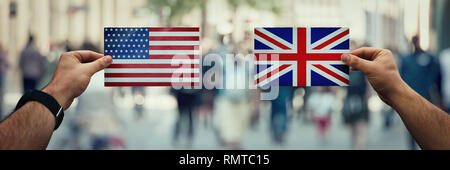 Two hands holding different flags, UK vs USA on politics arena over crowded street background. Future strategy, relations between countries. Cooperati - Stock Photo
