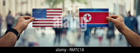 Two hands holding different flags, USA vs North Korea Republic on politics arena over crowded street background. Future strategy, relations between co - Stock Photo