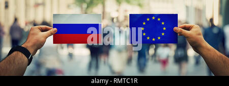 Two hands holding different flags, EU vs Russian Federation on politics arena over crowded street background. Future strategy, relations between count - Stock Photo