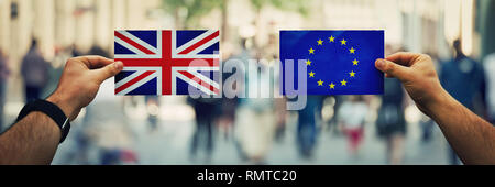 Two hands holding different flags, EU vs UK on politics arena over crowded street background. Future strategy, relations between countries after brexi - Stock Photo