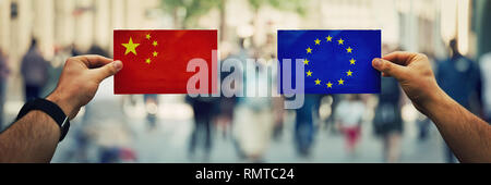Two hands holding different flags, EU vs China on politics arena over crowded street background. Future strategy, diplomatic relations between countri - Stock Photo