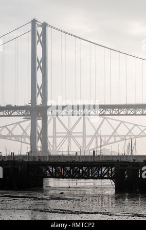 The old Forth Road bridge with the Forth Railway Bridge in the background on a misty day, Queensferry, Scotland - Stock Photo