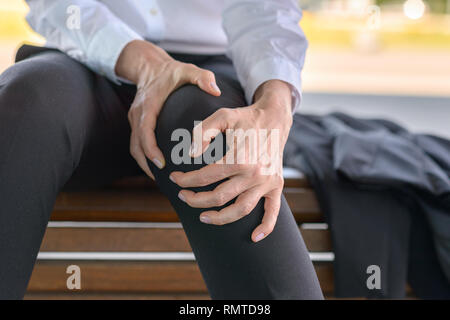 Businesswoman is holding her aching knee while sitting on a bench - Stock Photo
