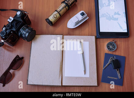 Notepad, passport, safety glasses, camera, phone and compass on a wooden background - Stock Photo