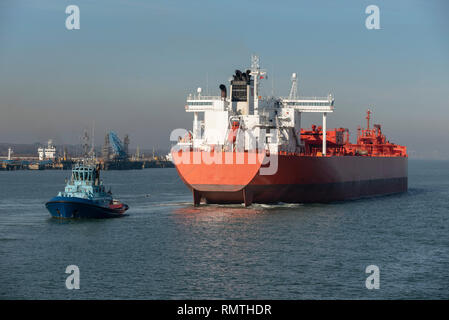 Tug with a stern line attached manouvering a crude oil tanker ship onto a berth at a refinery - Stock Photo