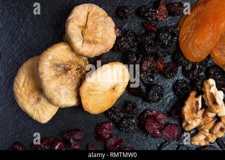 Theme is a sweet dessert made from natural products without sugar. Macro close up closeup dessert dried fruit set of walnut, cherry and cranberry rais - Stock Photo