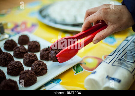 Hand holding a brownie in kitchen tong, with more brownies in the background, at farmer's market - Stock Photo