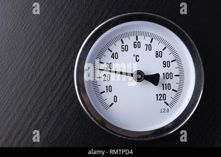 A clock thermometer for measuring the temperature with a reflection in the mirror. Thermometer on a glass mirror table. Black background. - Stock Photo