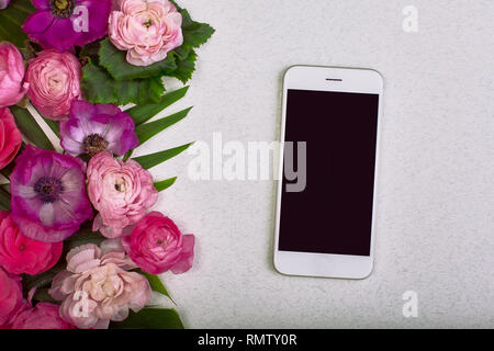 Beautiful floral background and green leaves, texture, wallpaper. Flat-lay of pink flowers with smartphone on gray background, top view, copy space - Stock Photo
