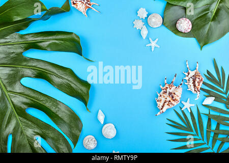 Summer female fashion flat lay. tropical palm branches and seashells on blue background. Beach, vacation, travel concept - Stock Photo