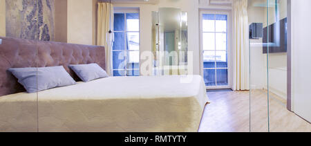 Big comfortable double bed in elegant luxary bedroom - Stock Photo