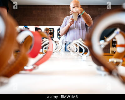 STRASBOURG, FRANCE - SEP 21, 2018: Apple Store with senior male customer admiring the new latest Watch Series 4 wearable devices with diverse straps taking photo on Nokia smartphone - Stock Photo