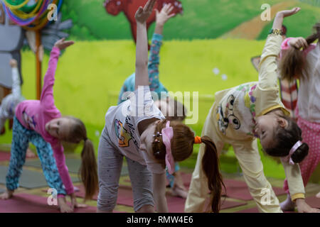 Children do yoga in pajamas with a professional teacher. - Stock Photo