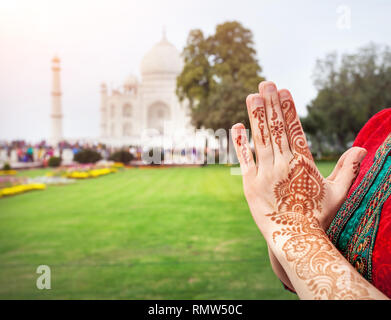 Woman hands with henna painting in Namaste gesture near Taj Mahal in Agra, Uttar Pradesh, India - Stock Photo