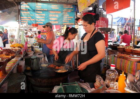 Mexican women cooking mexican food tacos and huaraches in the market. - Stock Photo