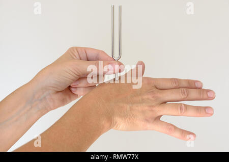 Anonymous person holding metal tuning fork against hand for therapy over white background. Includes copy space. - Stock Photo