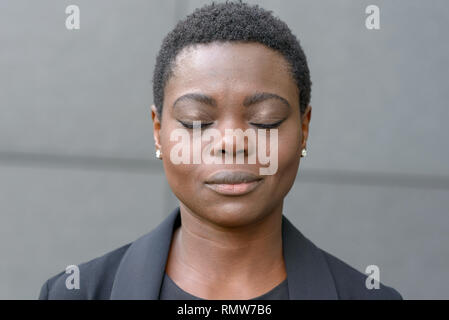 Bust portrait of black woman with short haircut and her eyes closed. Standing outside against grey wall in black jacket - Stock Photo