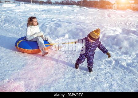 A little boy is dragging a tubing sling on rope on which the mother is sitting. Happy play in nature in winter. - Stock Photo