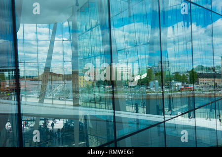 Oslo reflected in the glass at the new Opera house in Norway. - Stock Photo