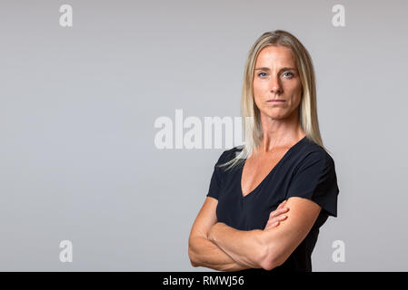 Attractive serious blond woman with a quiet friendly smile staring at the camera in a close up portrait isolated on grey - Stock Photo