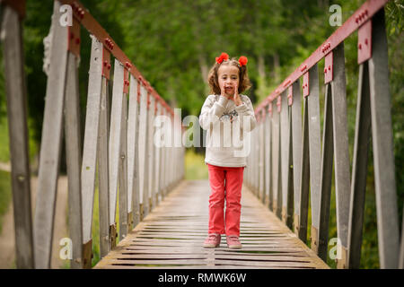 Cute little girl having fun in a rural bridge - Stock Photo
