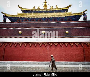 Lhasa, Tibet. 22th July 2016. Solitary man walks past a temple wall. Photo: Bryan Watt - Stock Photo