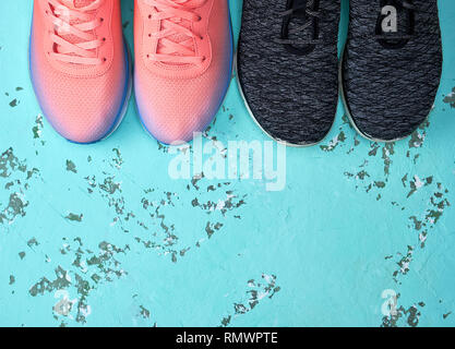 two pairs of sports sneakers on a green background, top view - Stock Photo