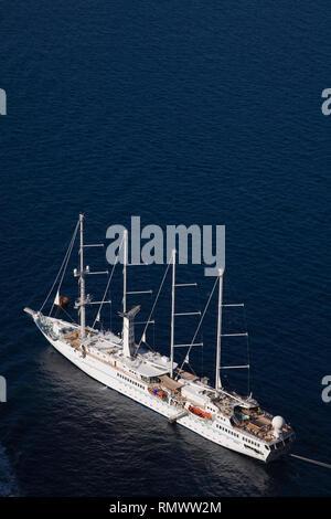 Luxury cruise sailboat moored off the coast of Santorini island, Greece - Stock Photo