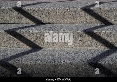 The handrails along these steps create a zig-zag shadow during afternoon sunlight in San Rafael, CA. - Stock Photo