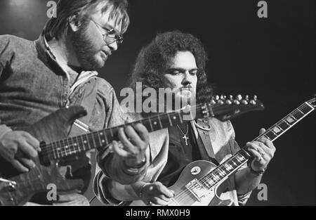 Guitarists Ed King and Gary Rossington are shown performing on stage during a 'live' concert appearance with the Lynyrd Skynyrd. - Stock Photo