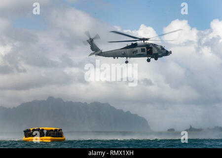 U.S. Marine Heavy Helicopter Squadron 463 and U.S. Sailors with Helicopter Maritime Strike Squadron (HSM) 37 wait for airlift from HSM-37's MH-60R Seahawk helicopter during a water rescue training event off the shore of Marine Corps Base Hawaii, Jan. 30, 2019. The purpose of the training is to make Marines and Sailors more proficient in water rescue operations. (U.S. Marine Corps photo by Lance Cpl. Porfirio Gonzalez)