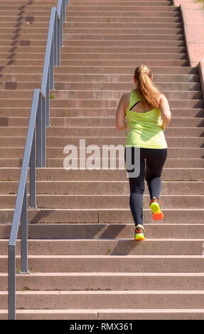 Full length rear view of an active and determined middle-aged woman running while climbing stairs during intense workout for weight loss outdoors in a - Stock Photo