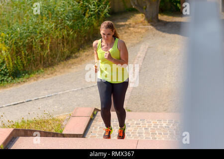 High angle view of a determined middle-aged woman running while climbing stairs during cardio workout outdoors in a sunny day of summer - Stock Photo