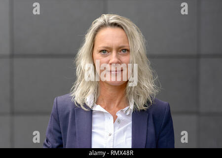 Mature attractive grey woman with tousled shoulder length hair looking intently at the camera with a quiet smile in front of a grey wall - Stock Photo