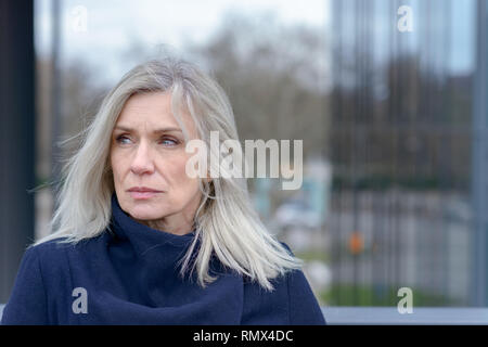Serious woman looking intently to the side with a thoughtful expression as she stands outdoors in town on a walkway - Stock Photo